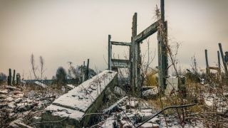 In the foreground, overgrown ruins of buildings, covered in a dusting of snow under a grey sky.