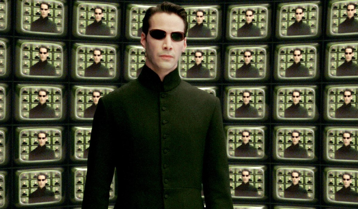 Keanu Reeves stands in front of The Architect's monitors in The Matrix Reloaded.
