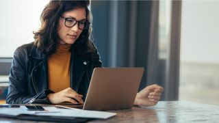 best business laptops: Business woman working on a laptop in an office