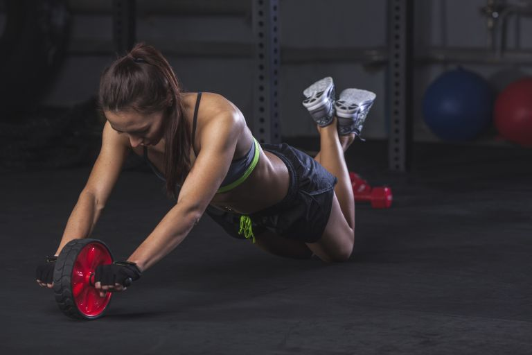 Woman doing an ab roller workout