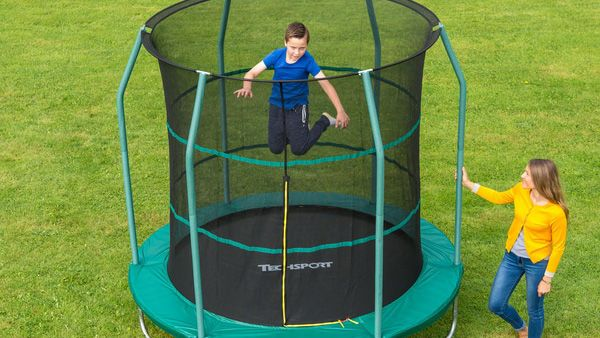 Best trampolines: Smyths Toys 8ft Trampoline with Safety Net in garden with child jumping and adult to side