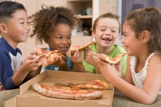 A group of children eat pizza.