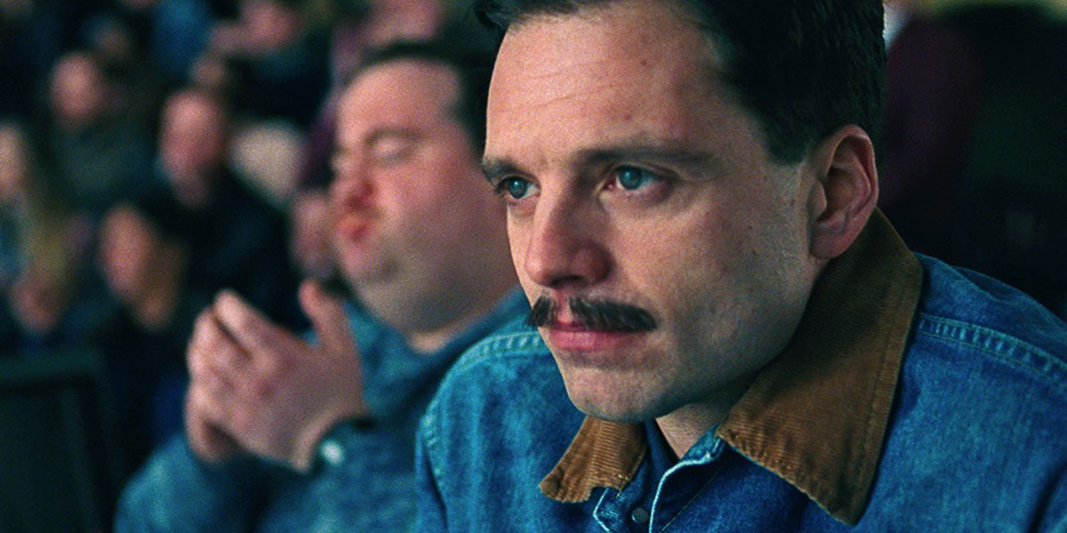 Sebastian Stan in I, Tonya with a denim jacket on watching ice skating with Paul Hauser in the background clapping.