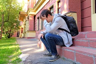 A teenager with a backpack sits outside a home, looking very sad.