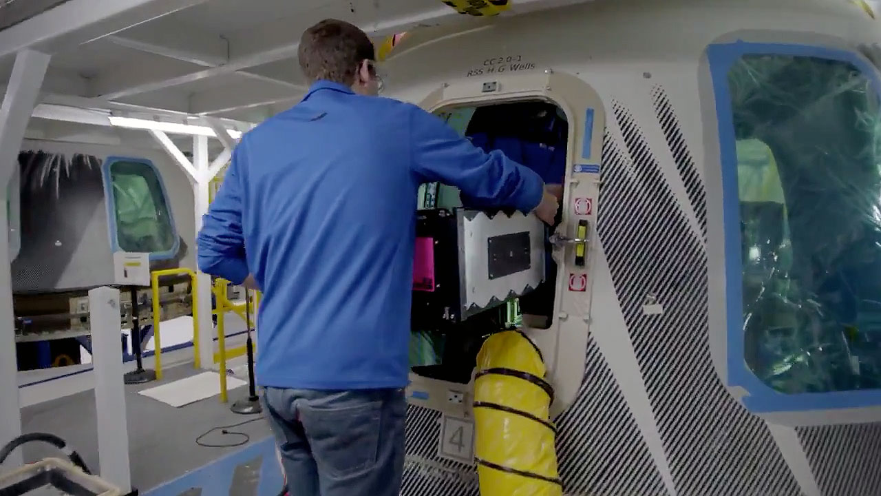 A Blue Origin employee loads the Club for the Future postcards into the company's New Shepard capsule, the RSS H.G. Wells, for their launch to space on Dec. 11, 2019.