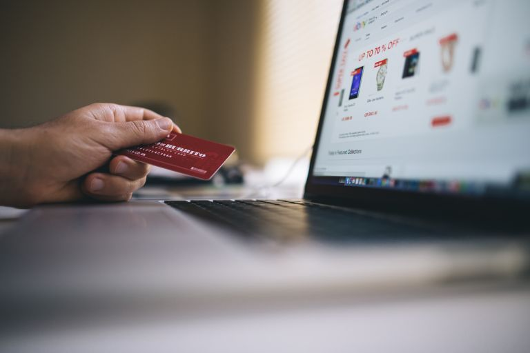 Online shopper using a computer and credit card to buy products online