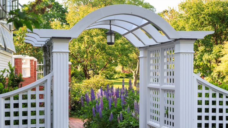garden arbor ideas: grey arch over path with hanging light