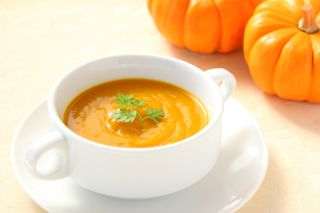 A pumpkin and a bowl of pumpkin soup