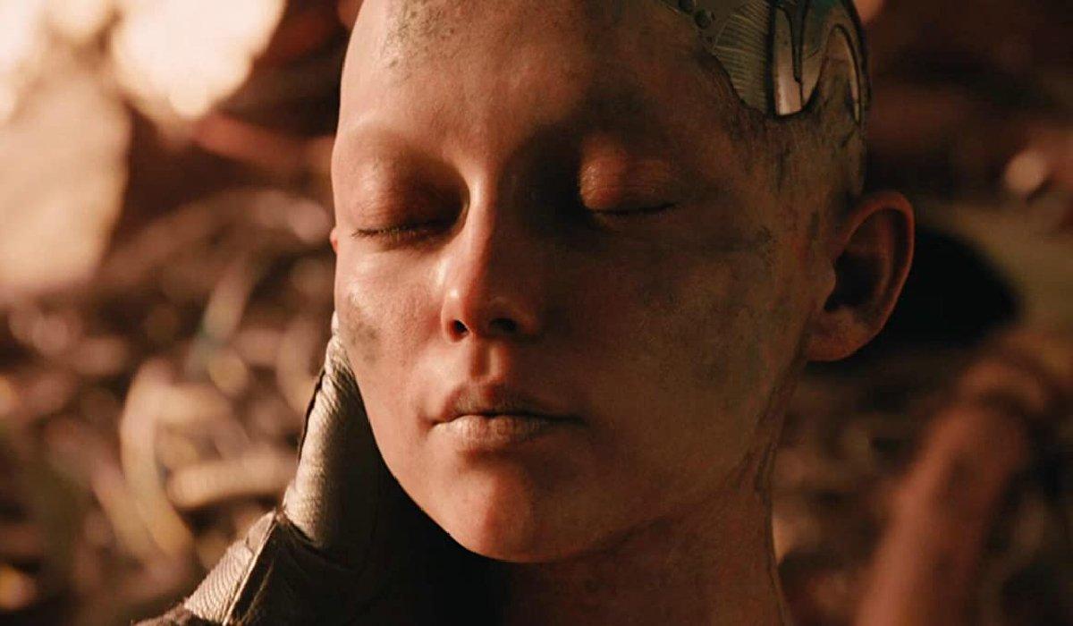 Alita: Battle Angel Alita's face held by Dr. Ido in the scrapyard