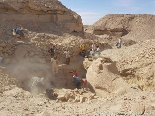"Workers dig a trench to excavate a large stone ""criosphinx"" (a sphinx with a ram's head) from quarry rubble at the Nile-side side of Gebel el-Silsila."