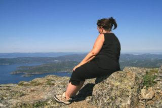 An overweight woman sitting outdoors on a rock.