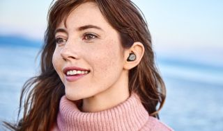 a woman wearing the jabra elite 7 pro true wireless earbuds