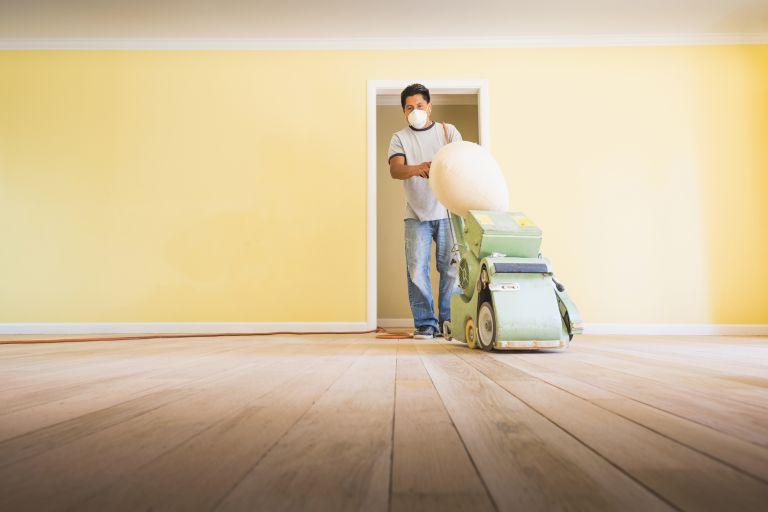 Man refinishing hardwood floors