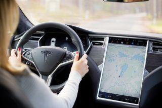 Woman driving Tesla Model S electric car