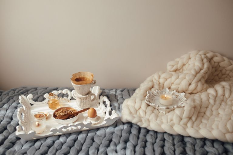 Cup with filter coffee, organic granola with honey on grey and beige wool merino giant plaid. Comfortable at home, happy mood and leisure cozy morning concept, hygge home decor