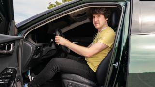 Driver sitting in driving seat of blacked out Kia EV6