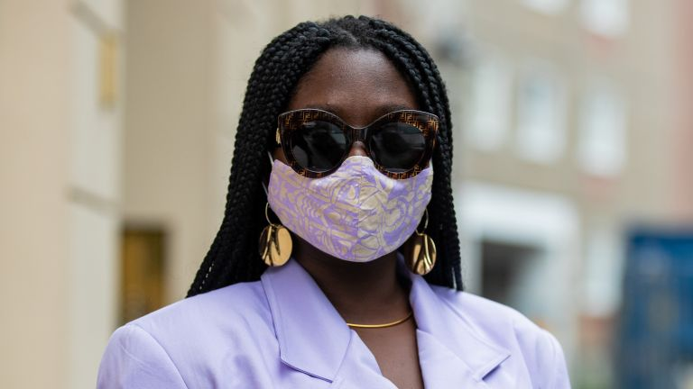 Lois Opoku is seen wearing face mask Nada Dehni, purple blazer Pyer Moss, Bottega Veneta bag in turquoise, Zara pants with graphic print, Fendi sunglasses, Prada sandals on September 04, 2020 in Berlin, Germany