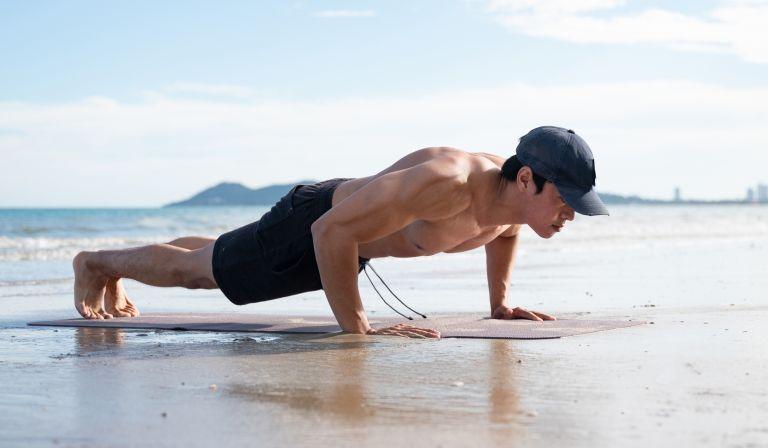 Asian man doing push ups on the beach