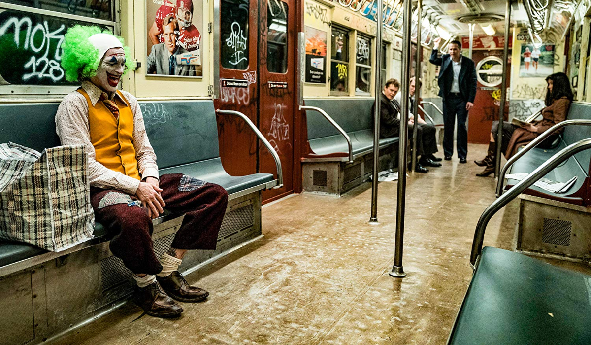 Joker Arthur laughing on the subway in his full clown outfit
