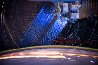 A long-exposure photo shows the trails of Earth and stars moving around the International Space Station.