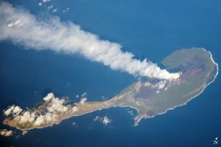 A steam plume drifts away from a volcano on Pagan Island, part of the Commonwealth of the Northern Marianas.