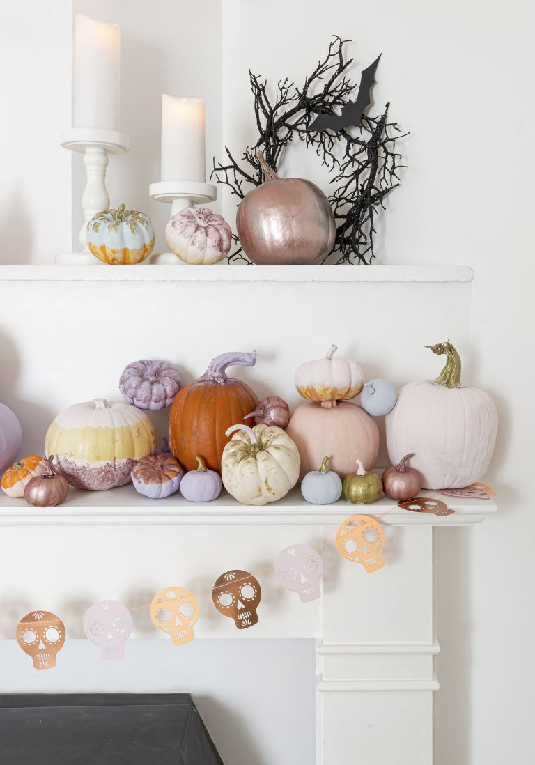 Mixture of pumpkins decorated with metallic paint on a mantel with skull garland