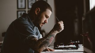 A tattooed creative man works