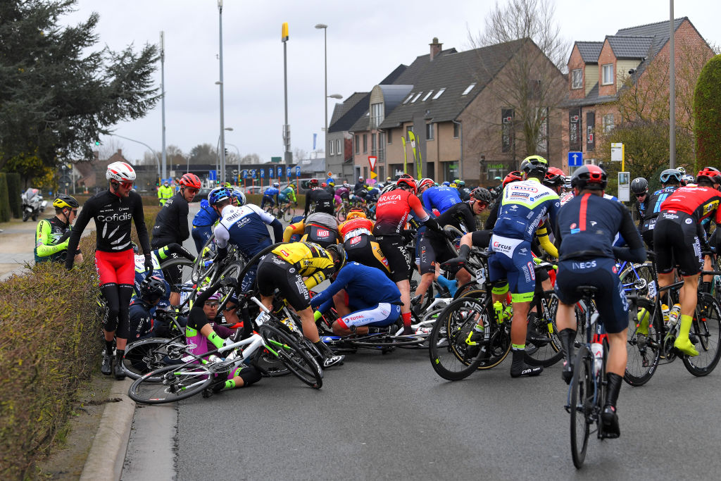 NOKERE BELGIUM MARCH 17 The peloton during the 75th Nokere Koerse Danilith Classic 2021 Mens Elite a 1955km race from Deinze to Nokere Crash Injury NokereKoerse on March 17 2021 in Nokere Belgium Photo by Luc ClaessenGetty Images