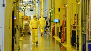 Photograph taken inside an Intel semiconductor fabrication plant showing person in overalls (bunny suit) walking past lithographic equipment.