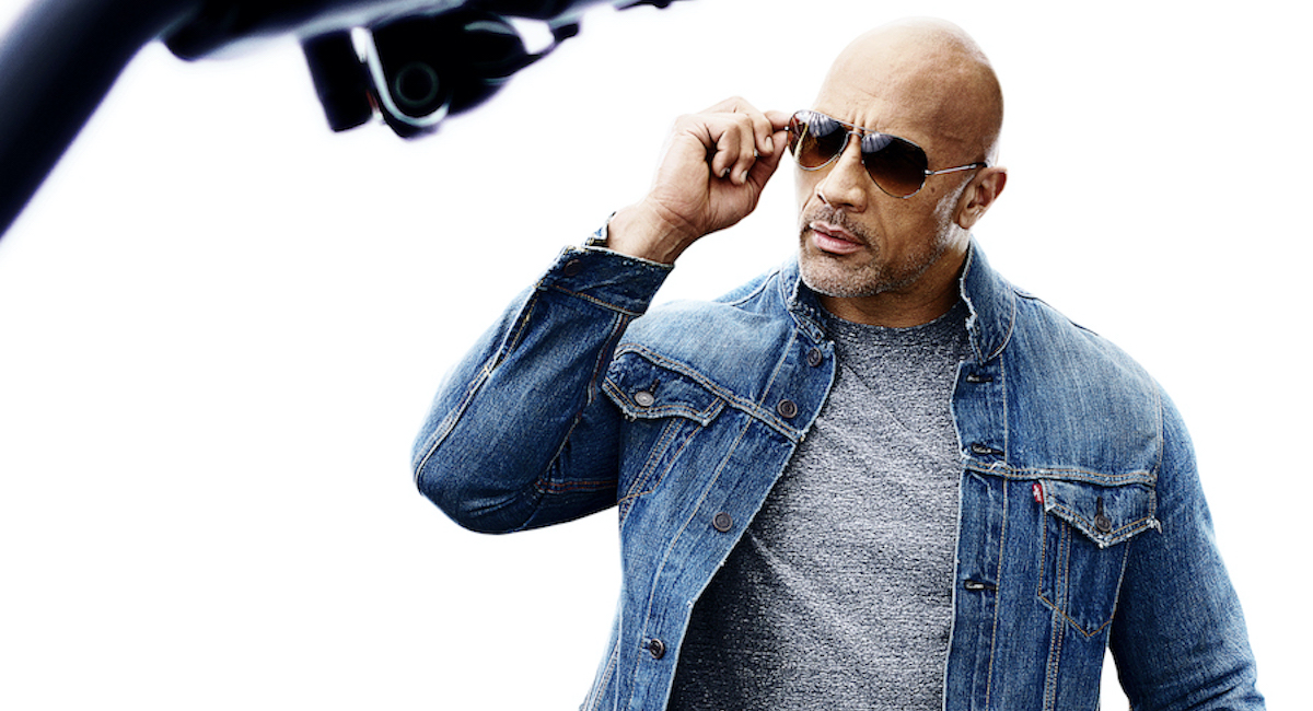 Dwayne Johnson in sunglasses and a denim jacket.
