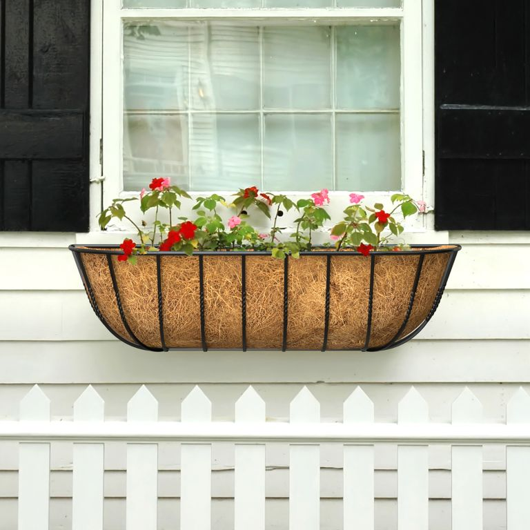 Coconut husk lined window box on white cladded panel house exterior with blue