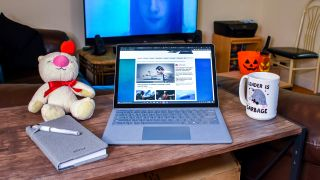 Surface Laptop 4 on a coffee table next to a notebook and a coffee cup