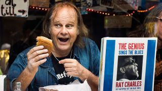 A portrait of walter trout eating a burger with some records