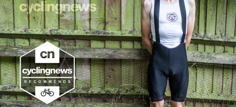 Invani men's bib shorts worn by rider standing alongside wooden fence