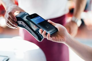 Hand pays taps payment card on card reader, screen shows secure payment representing PCI compliance