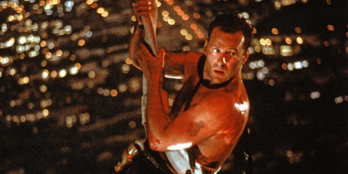 John McClane hanging by a fire hose in Die Hard