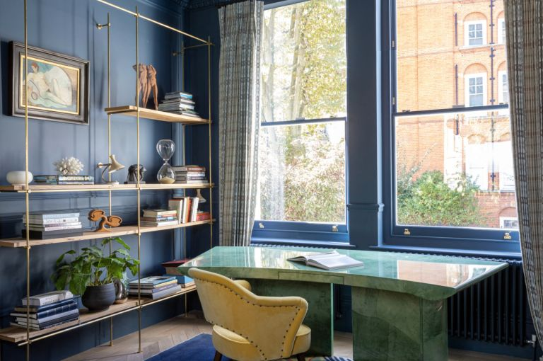 Home office with blue walls and green desk