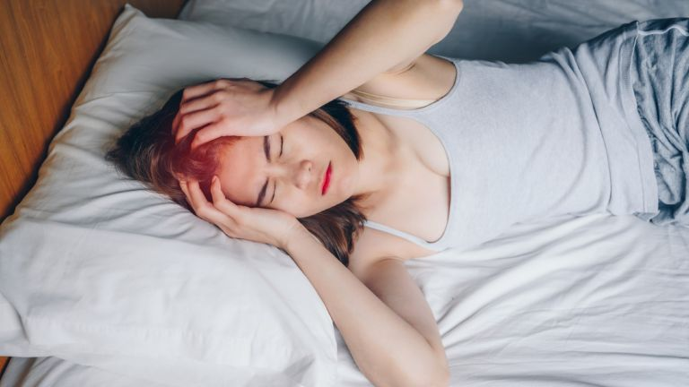 woman having headache while she lying on bed, why do I keep dreaming about my ex