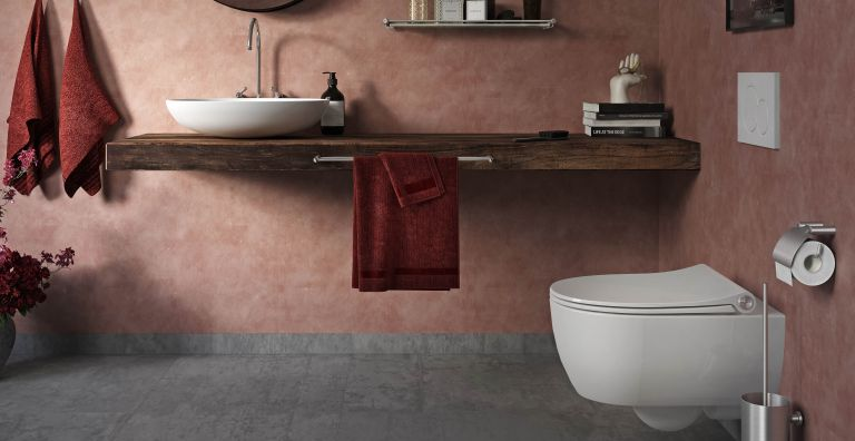 white sleek toilet seat in pink bathroom