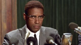 Denzel Washington sitting in front of several microphones in Malcolm X.