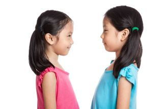 Asian twins girls smile look at each other isolated on white background.