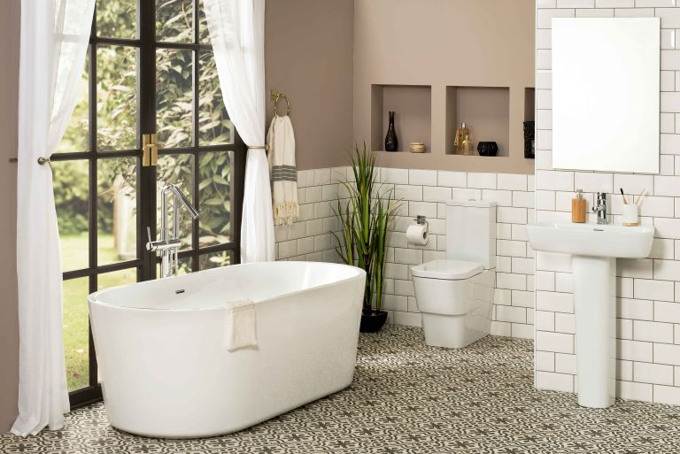downstairs bathroom with a freestanding modern bath, white metro tiles and soft pink walls