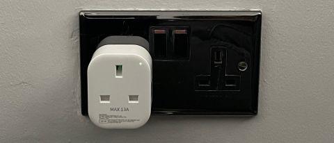The Meross Smart Wi-Fi Plug Mini MSS110 plugged into an electrical socket on a gery wall