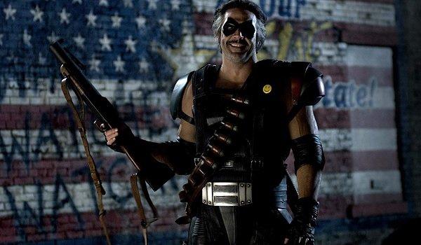 Watchmen Jeffrey Dean Morgan looking twisted with a shotgun