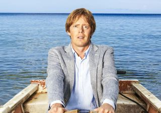 Death in Paradise Season 5 — DI Humphrey Goodman in a rowing boat