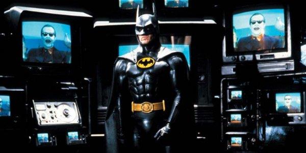 Batman standing in front of The Joker on TV monitors