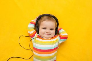 Happy baby wearing headphones.
