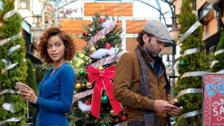A woman and a man look at their phones in front of some highly decorated Christmas trees