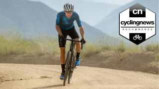 A cyclist riding one of the best gravel bikes under £2000 on a dirt road