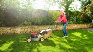 What are self-propelled lawn mowers? A woman wearing a red top uses a lawn mower to cut the grass on a sunny day